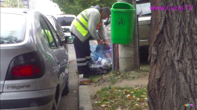 Angajat al primăriei, răscoleşte prin gunoi